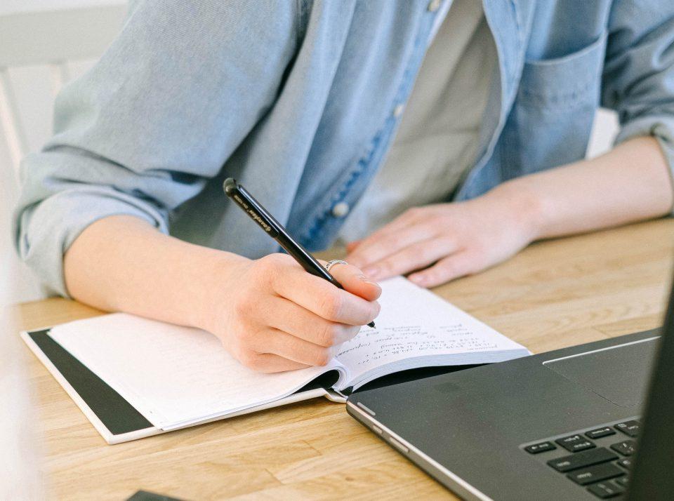 Person beim Schreiben in ein Notizbuch neben einem Laptop (Foto: Pexels/Ivan Samkov)
