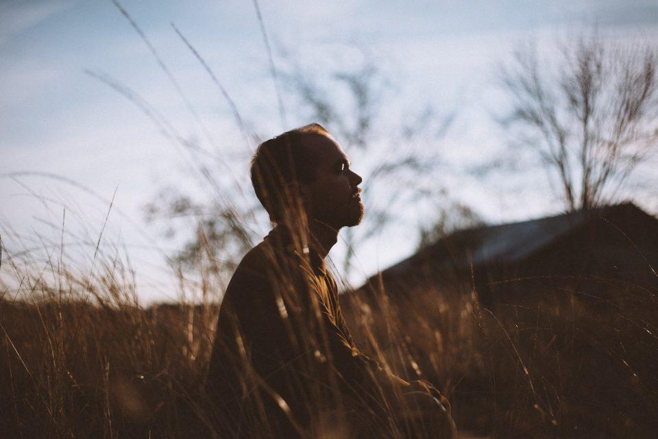 Mann sitzt Wiese hohes Gras Abend ruhig Sonnenuntergang Meditation im Sitzen