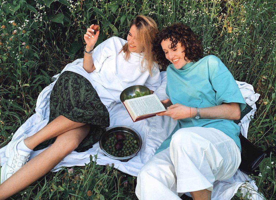 November Zwei Frauen Gras Picknick Obst Freude Lesen Spass Freundinnen Quality Time Anastasiia Rozumna BYJs Ykv Qs Unsplash Cropped
