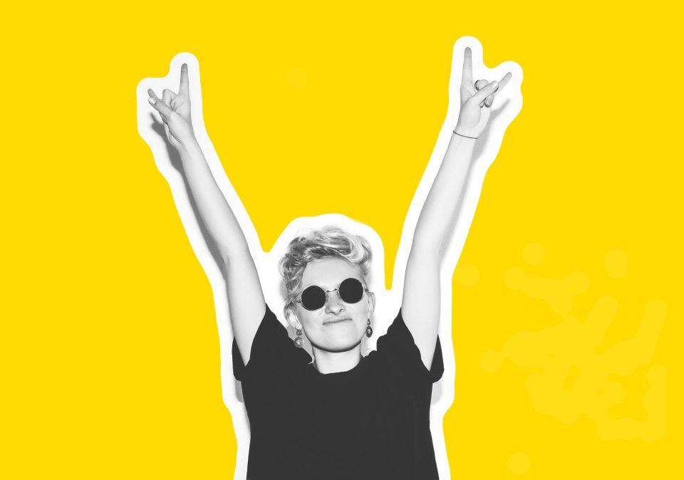 Weltkrebstag Kurvenkratzer Weltkrebstag Frau Selbstbewusst Sonnenbrille Arme Geste Siegespose Schwarzweiss Gluecklich Gelb Shutterstock_