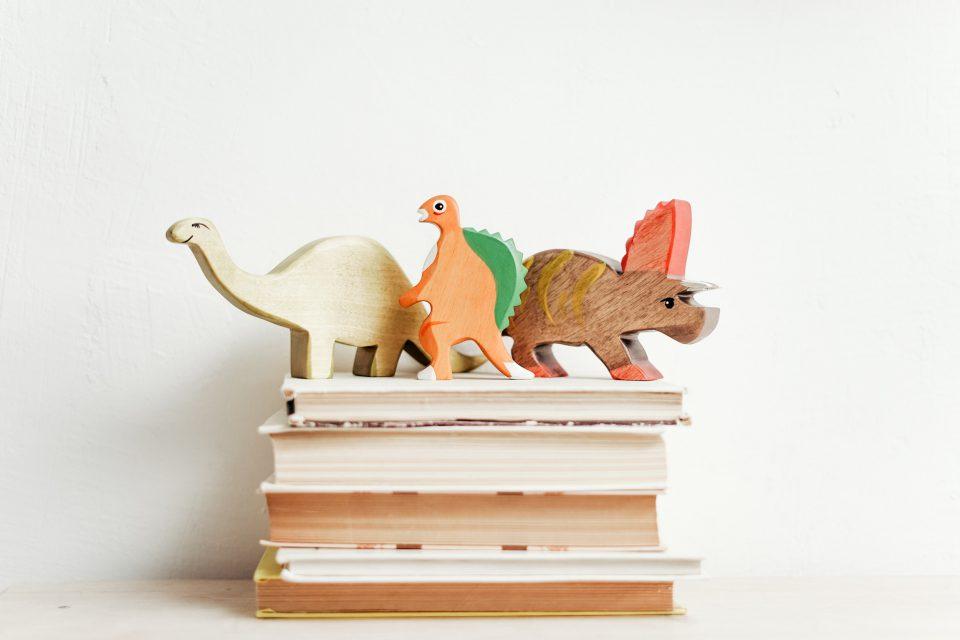 Kinder Buecher Stapel Dinosaurier Holzfiguren Bunt Weiss Pexels Cottonbro Cropped