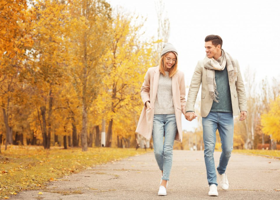 Young Couple Walking In Park On Autumn Day