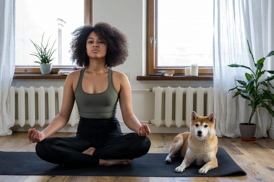 Meditierende Frau im Schneidersitz mit Hund