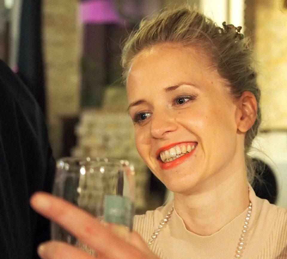 Julia Keita Frau Blond Lippenstift Rot Glas Hand Lachen Feierlich Kette Julia Keita Frueher_impulsiv_V